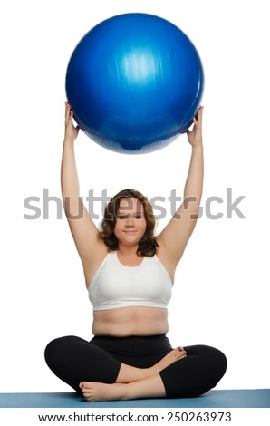 fat woman practicing yoga with blue ball on mat - stock photo