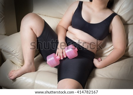 fat woman tired give up exercise concept hand drop dumbbell sitting on sofa - stock photo