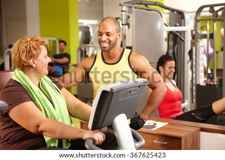 Fat woman training on exercise bike with personal trainer. - stock photo