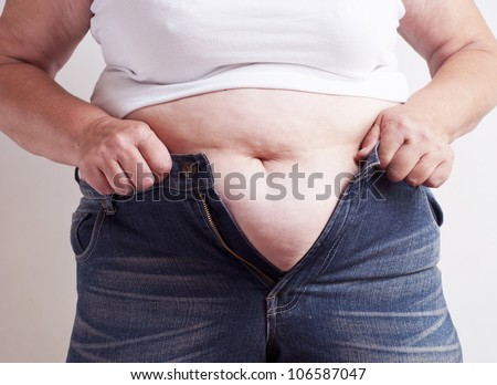 Fat woman trying to wear jeans - stock photo