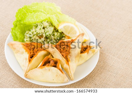 Fatayer - Arab pastry filled with spicy meat. Served with tabbouleh and lemon wedges. - stock photo