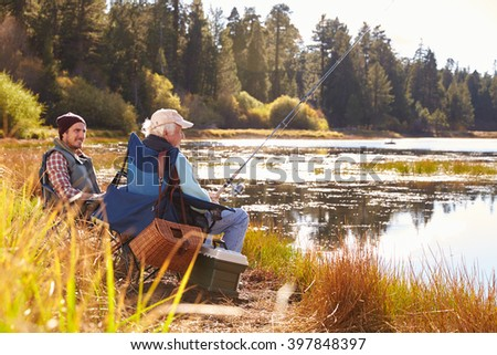 Father and adult son fishing lakeside, Big Bear, California - stock photo