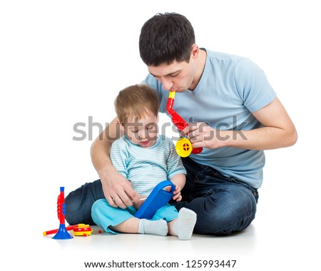 Father and baby boy having fun with musical toys. Isolated on white background - stock photo