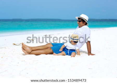 Father and baby boy sitting with panama hats and sunglasses on white sandy beach on Maldives - stock photo
