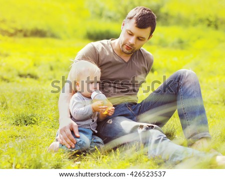 Father and baby drinks from a bottle sitting on grass summer  - stock photo