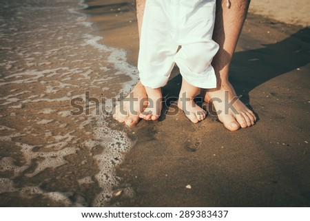 father and baby feet walking on sand beach - stock photo