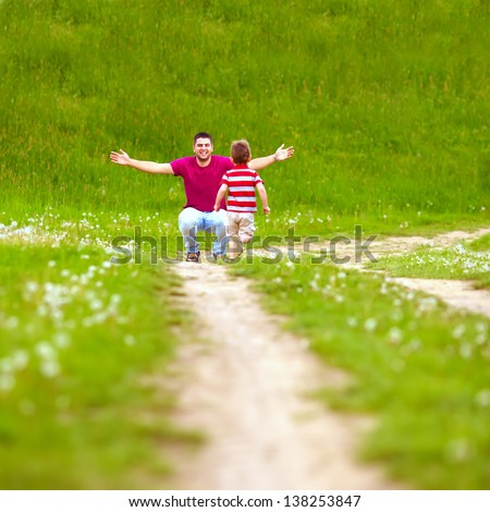 father and baby having fun, playing on green field - stock photo