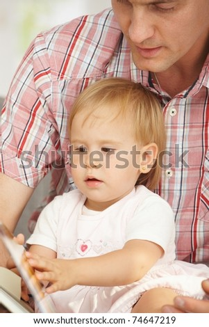 Father and baby sitting together and reading story book.? - stock photo