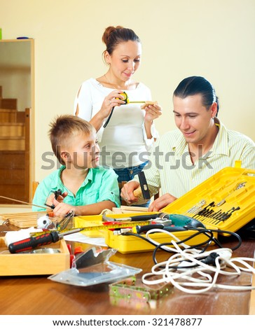 Father and boy spend their free time with working tools at home, happy  woman helping them   - stock photo