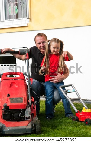 Father and Child mowing the lawn together, daughter has a wheelbarrow and helps daddy getting rid of the lop - stock photo