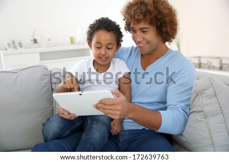 Father and child playing with digital tablet - stock photo
