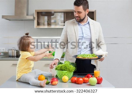 Father and child preparing pizza together - stock photo