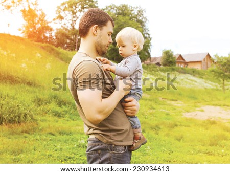 Father and child together outdoors in summer warm day countryside - stock photo