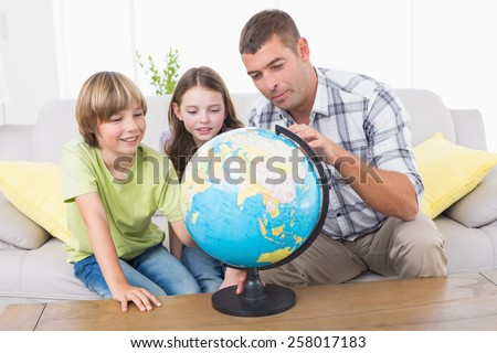 Father and children exploring globe in living room - stock photo