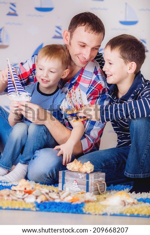 father and children playing boats - stock photo
