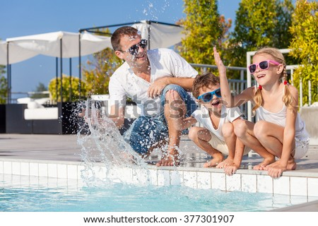 Father and children playing near a swimming pool  at the day time. Concept of friendly family. - stock photo