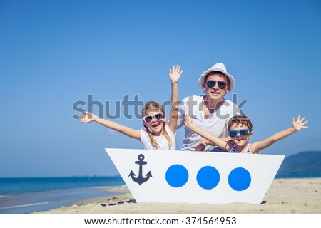 Father and children playing on the beach at the day time. Concept of friendly family. - stock photo