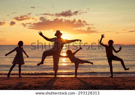 Father and children playing on the beach at the sunset time. Concept of friendly family. - stock photo