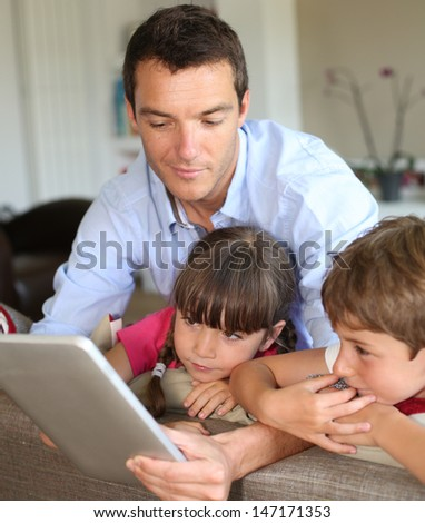 Father and children playing with tablet at home - stock photo