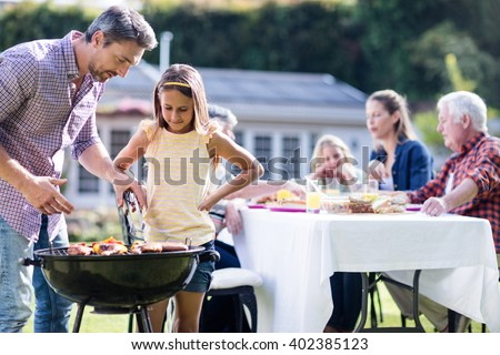 Father and daughter at barbecue grill while family having lunch in the garden - stock photo