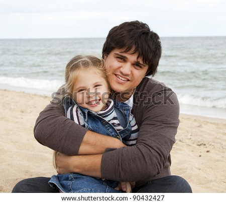 Father and daughter at the beach in fall. - stock photo