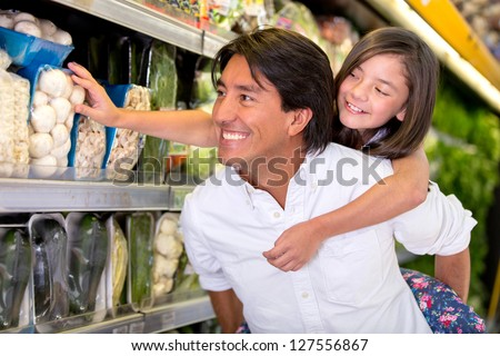 Father and daughter buying groceries at the supermarket - stock photo
