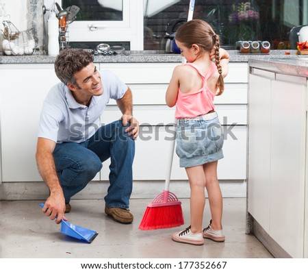 Father and daughter cleaning in the kitchen, sweep floor at home, man little girl family - stock photo