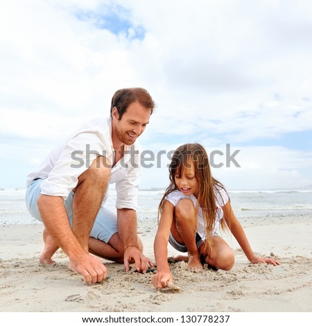 Father and daughter day at the beach collecting shells together having fun and smiling - stock photo