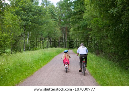 father and daughter doing a bicycle tour - stock photo