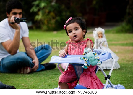 father and daughter, father taking pictures or making film of his daughter in sunny afternoon. man making film with handycam - stock photo