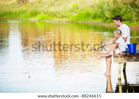 Father and daughter fishing on the lake - stock photo