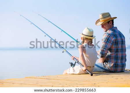 Father and daughter fishing on the pier - stock photo
