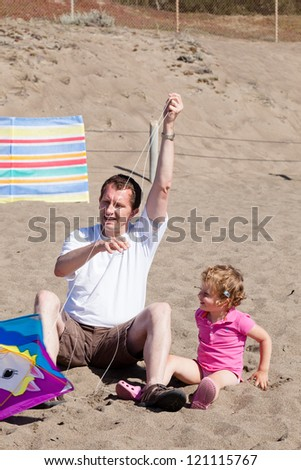 Father and daughter flying kite on the beach on sunny day. - stock photo