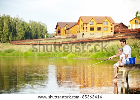 Father and daughter go fishing on the lake - stock photo