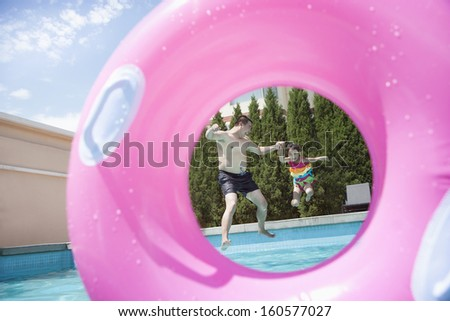 Father and daughter holding hands and jumping into the pool, seen through an inflatable pink tube - stock photo