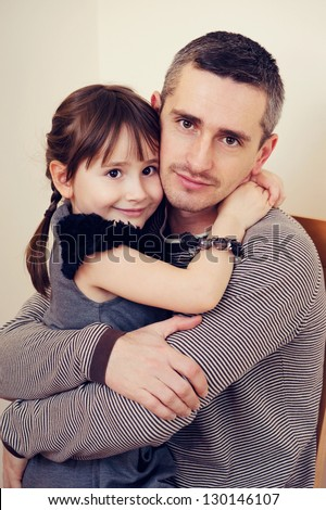 Father and daughter hugging and smiling - stock photo