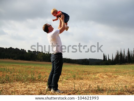 father and daughter in the autumn meadow - stock photo
