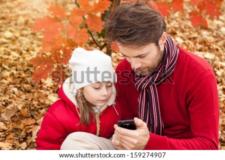 Father and daughter looking at the mobile phone while sitting outdoor in an autumn park - enjoying modern technology - stock photo