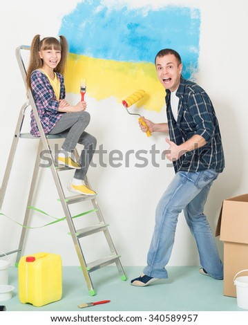Father and daughter makes repairs at home - painting big Ukrainian flag on wall at home. - stock photo