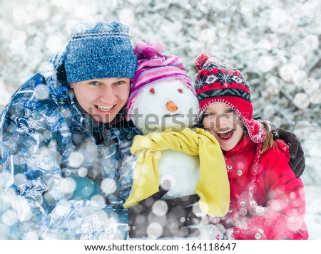 Father and daughter making a snowman - stock photo