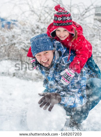 Father and daughter molded ball of snow for a snowman - stock photo