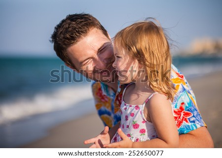 Father and daughter on the beach near the sea. Young man hugs little baby girl. It is emotional scene of relations between child and parent - stock photo
