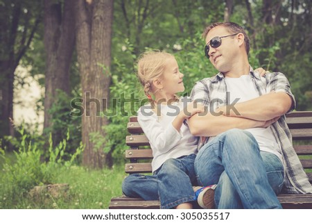 Father and daughter playing at the park at the day time. Concept of friendly family. - stock photo