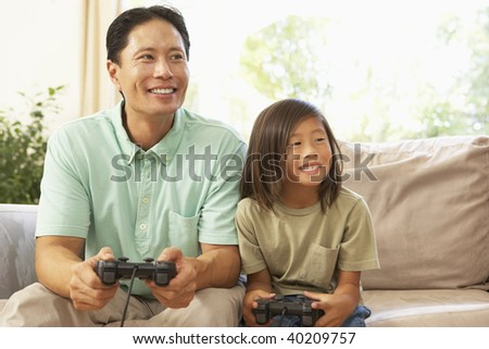 Father And Daughter Playing Computer Game At Home - stock photo