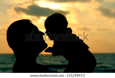 father and daughter playing on the beach at sunset - stock photo
