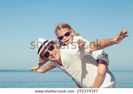 Father and daughter playing on the beach at the day time. Concept of friendly family. - stock photo