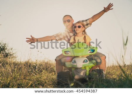 Father and daughter playing on the road at the day time. They driving on quad bike in the park. People having fun on the nature. Concept of friendly family. - stock photo
