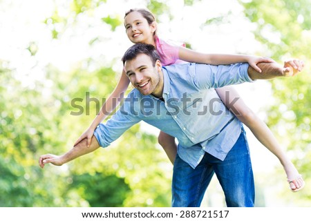 Father and daughter playing outdoors  - stock photo