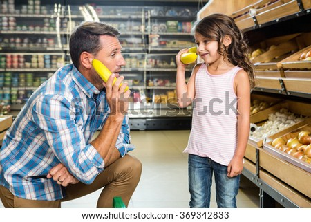Father and daughter playing with bananas in grocery store - stock photo