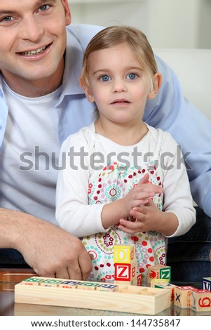 Father and daughter playing with blocks - stock photo